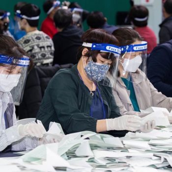 group of people sitting with wearing of covid masks