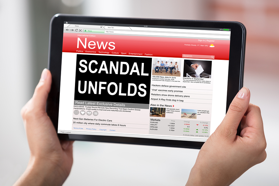 Hands Holding A Digital Table With A Screen Showing Unfolds Scandal News